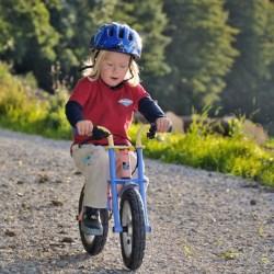 Ein Junge auf seinem Laufrad braust den Berg hinab und nimmt die Füße hoch.
