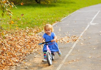 Kleines Mädchen auf einem Laufrad im Herbst unterwegs